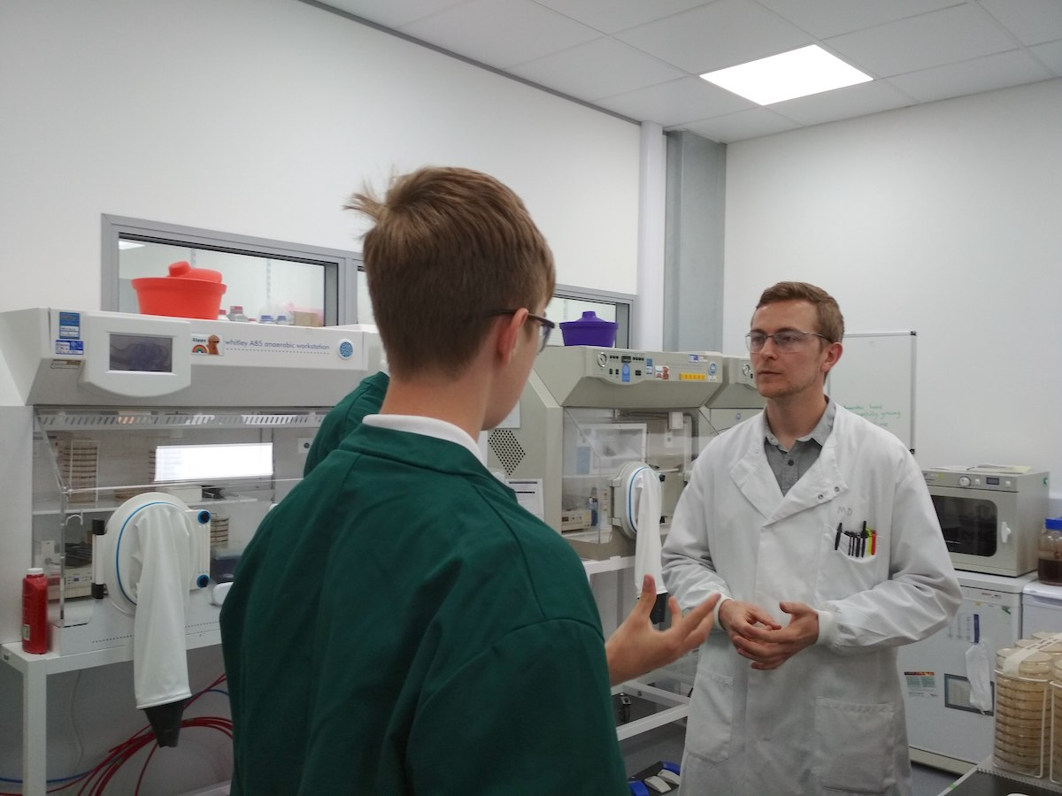 Secondary school students in a lab asking a microbiologist questions