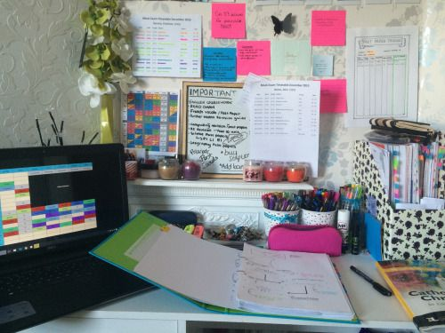 Student desk set up with a laptopn, open folder of notes, pens and other revision materials