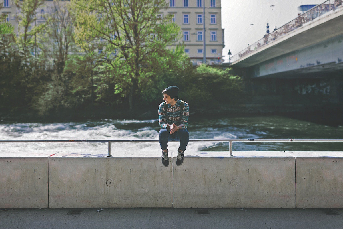 Young student in a beanie hat sitting in front of a river in a city