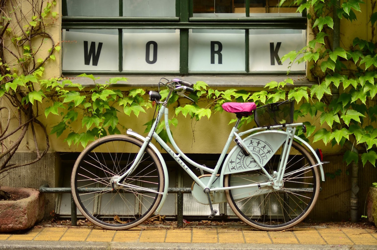 Green bicycle in front of a building with the Work in front of it