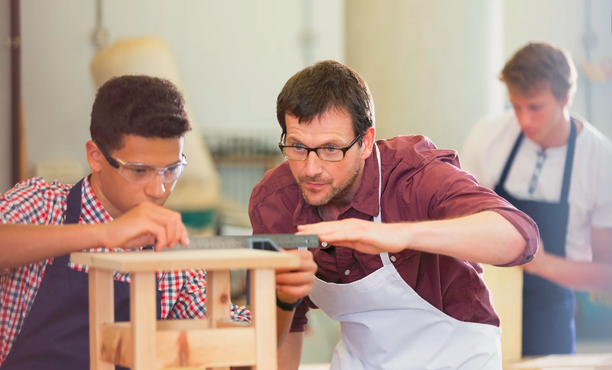 Teacher working with secondary school students in a Design and Technology class