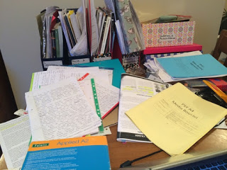 Messy student desk strewn with notes, books and exam papers