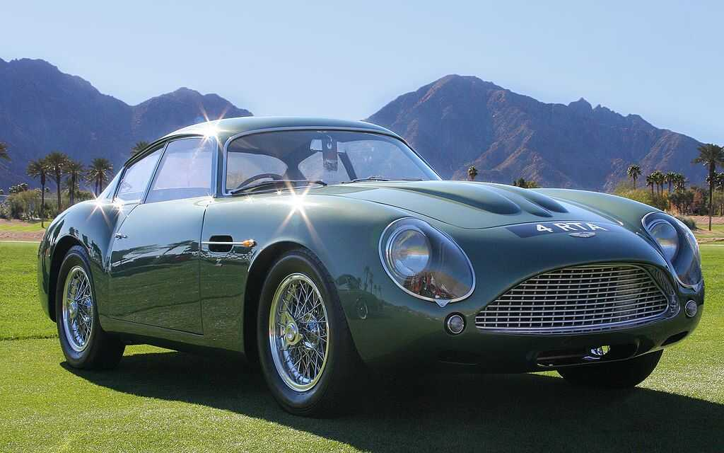 A vintage green Aston Martin sitting outside with mountains in the background