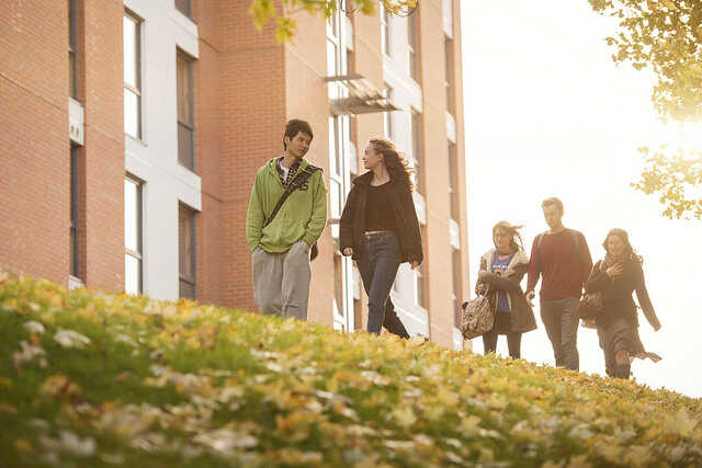Students walking across the park outside Birks Grange Village at the University of Exeter