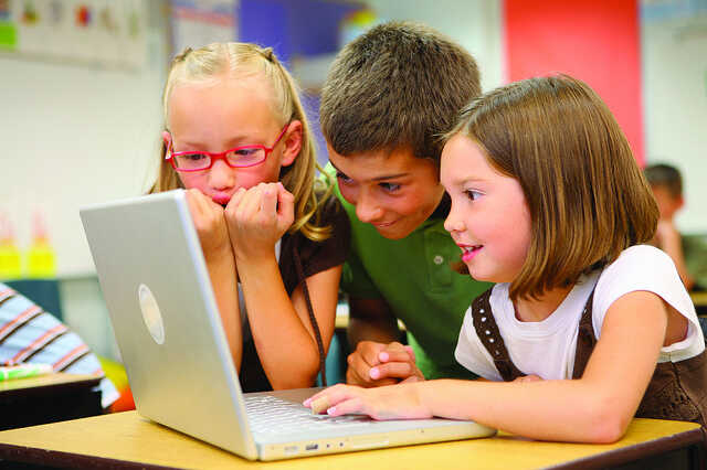 Three young children crowding round a laptop