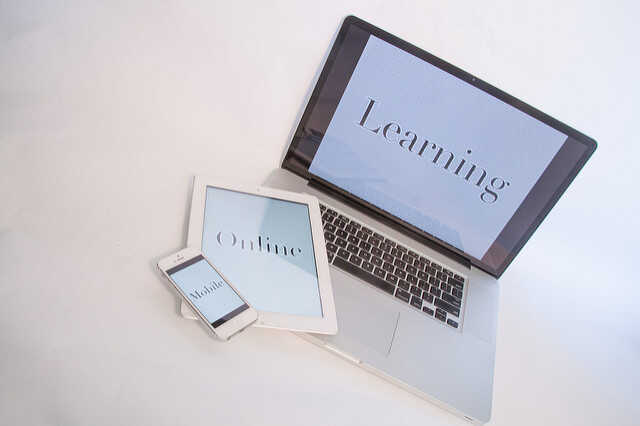A MacBook with the word Learning on it, a table with the word Online on it and a smartphone with the word Mobile on it