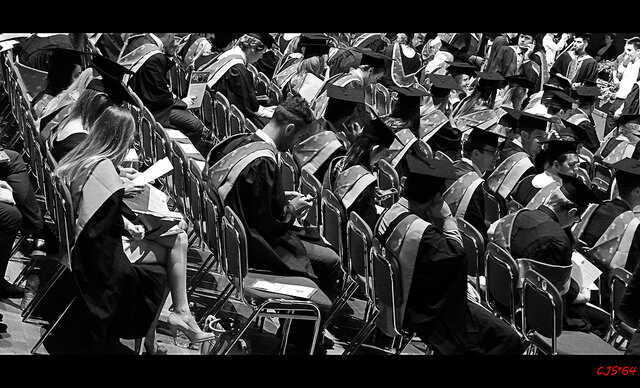 Black and white image of graduates sitting during their graduation