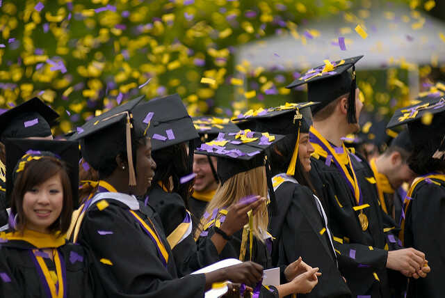 Graduates dressed in their robes and mortarboards covered in purple and yellow confetti