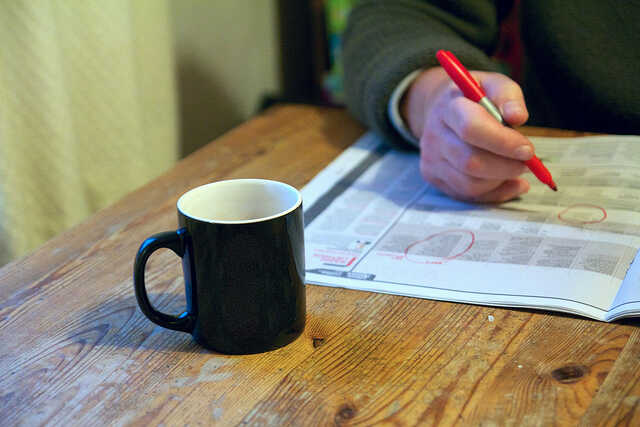 Man highlighting information in a newspaper with a cup of coffee