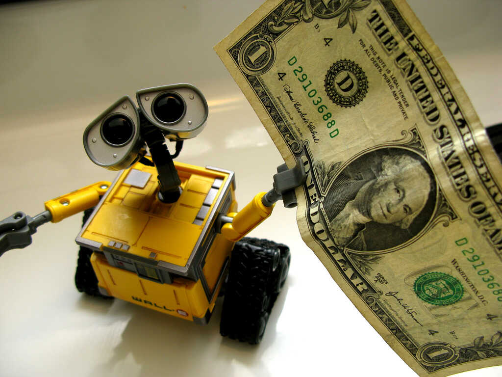 Yellow toy robot holding a one dollar note