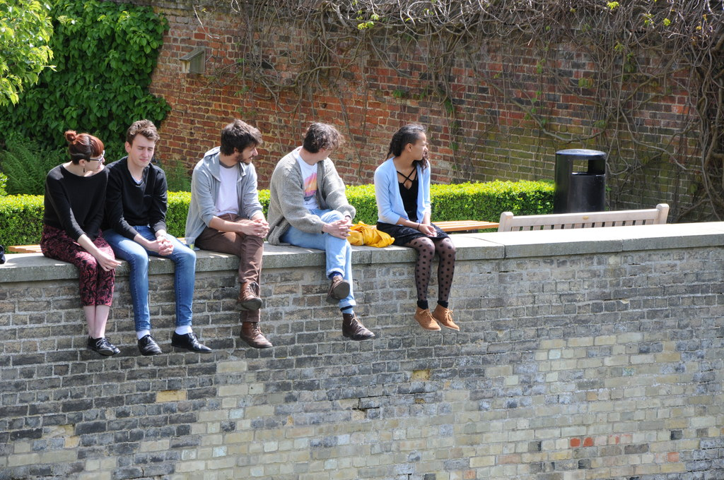 Five young people sitting on a wall