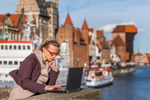 A young woman on her laptop with a Gdansk in the background