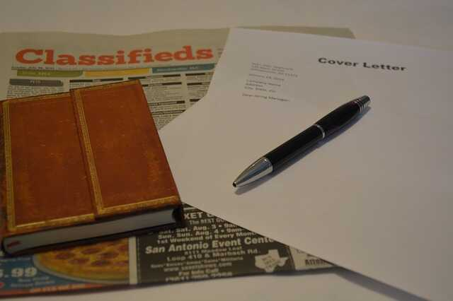 Classified pages of a newspaper open on the table alongside cover letter notes, a pen and notebook