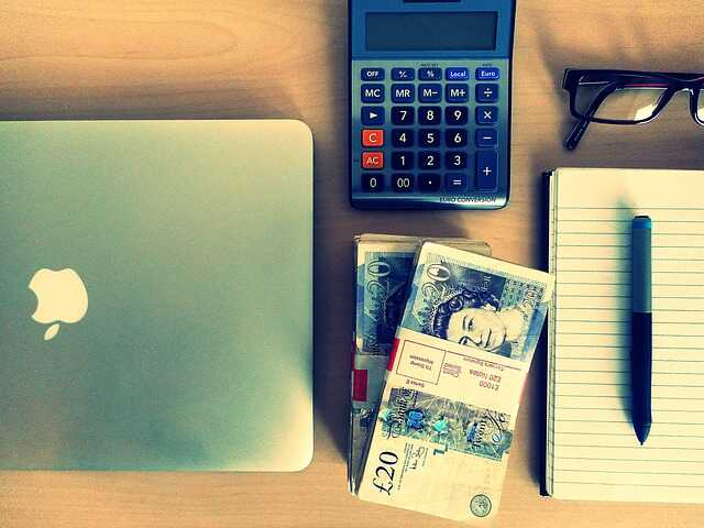 Twenty pound notes, a notebook and pen, a MacBook, a calculator and glasses on a table