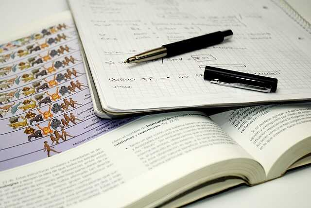 A close up of a squared notebook, Parker pen and biology textbook