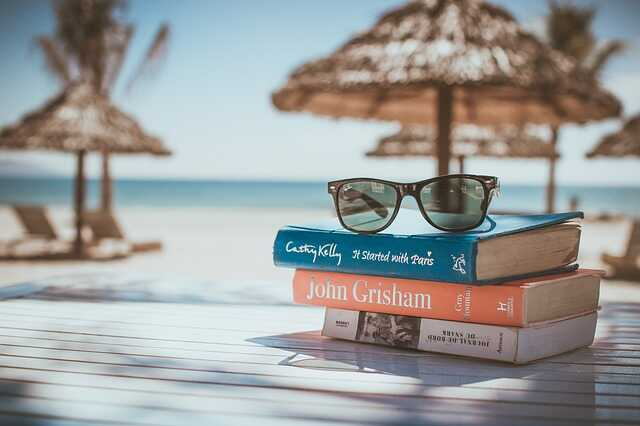 Three books and a pair of sunglasses on a table in front of the seashore