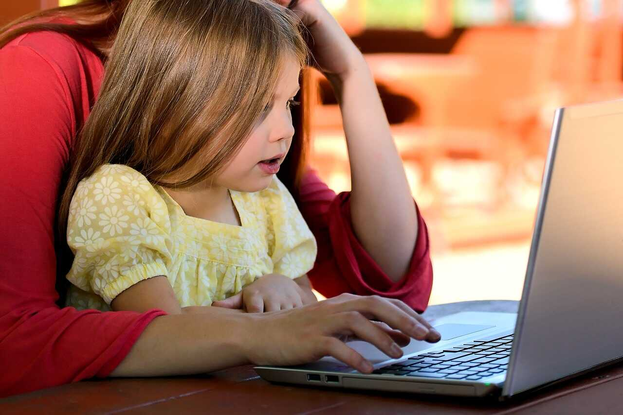 Girl sitting on her parent's lap looking at a laptop