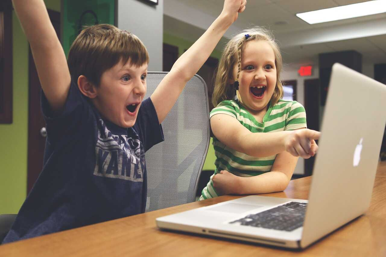 Two children excited from something on their laptop screen