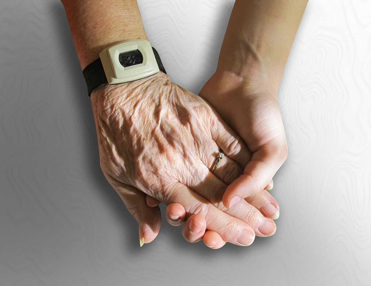 Older person's hand and younger person's hand holding one another