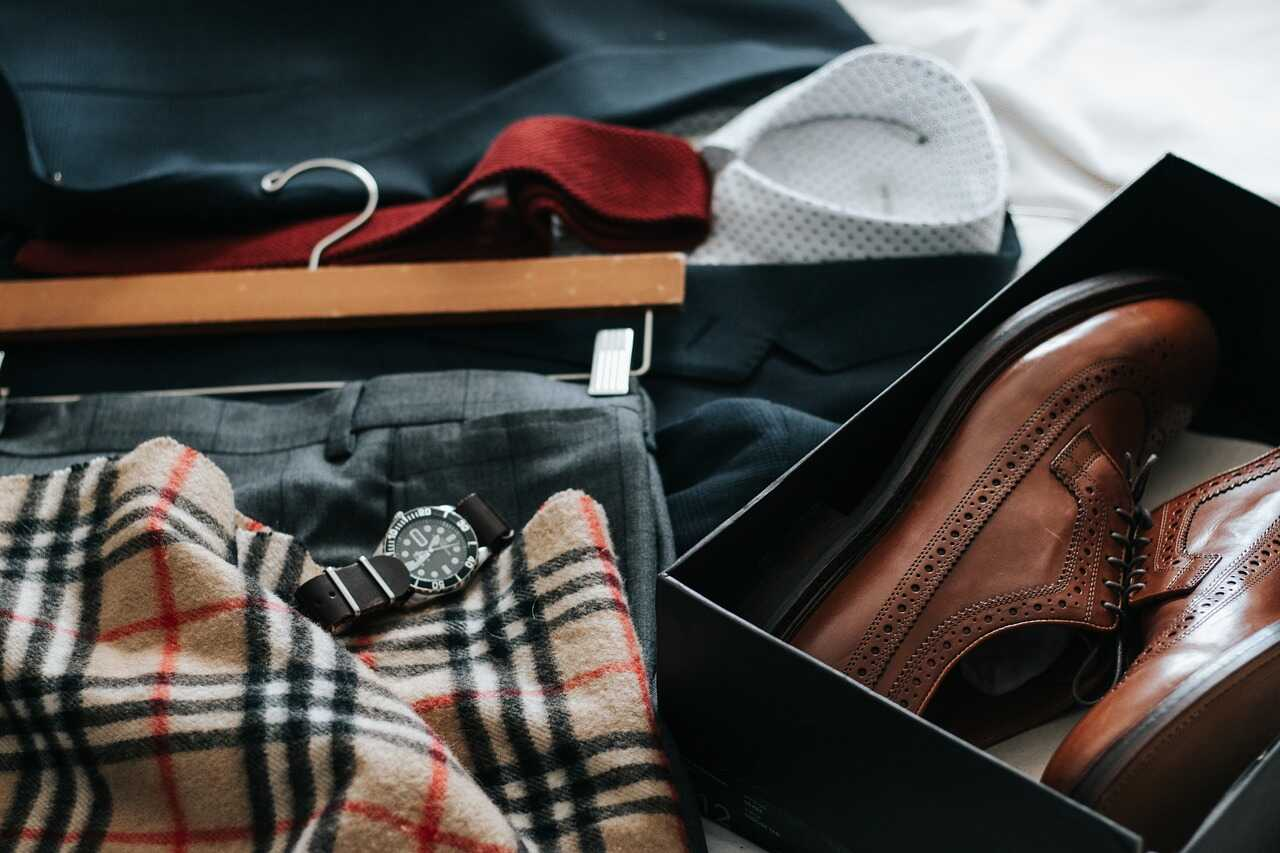 Professional clothes laid out on a bed including a watch and leather shoes in a box