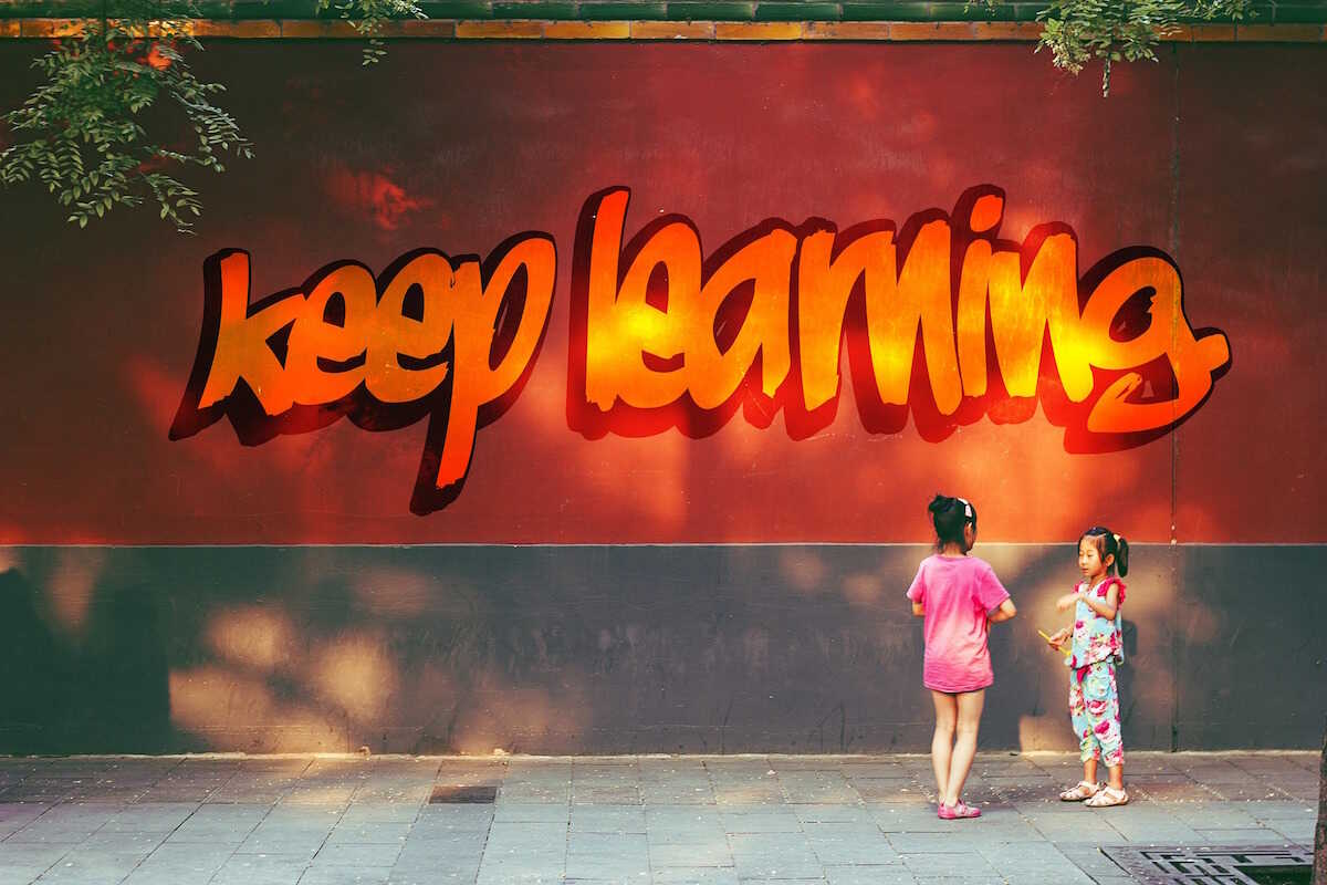 Two children standing in front of a wall saying Keep Learning