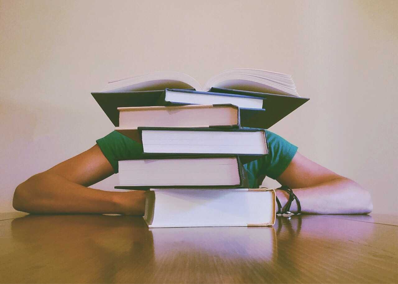 Student with his head on the table behind a pile of books