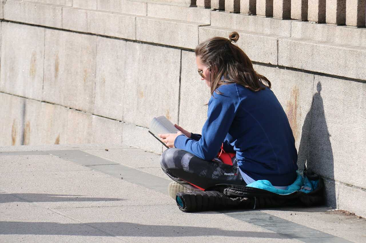 Female student sitting in the sun reading a book