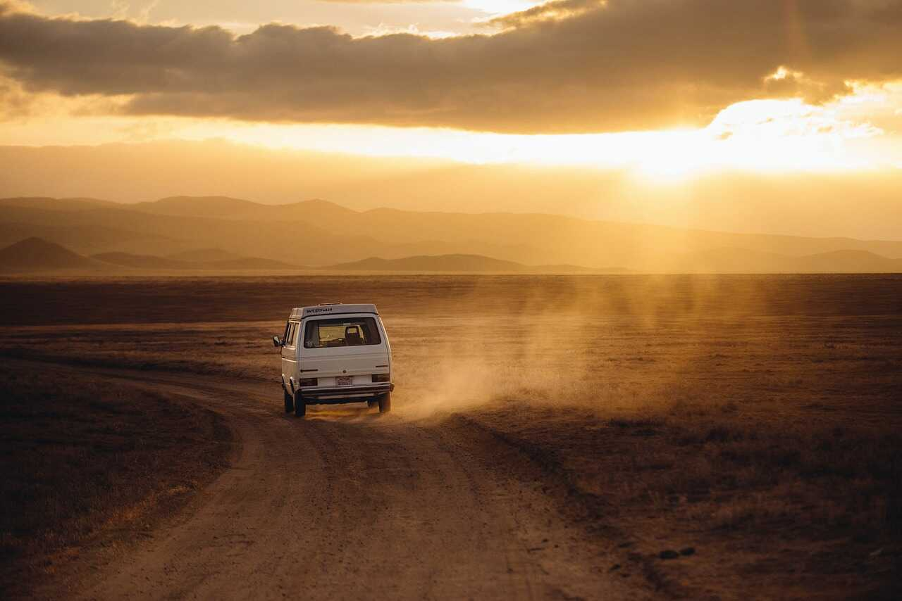 Campervan driving on a dirt track in the desert