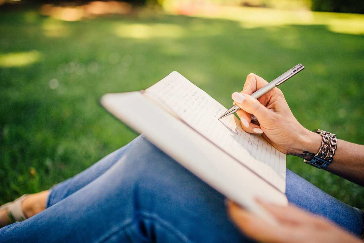 Close up of a woman sitting in the park writing in her notebook