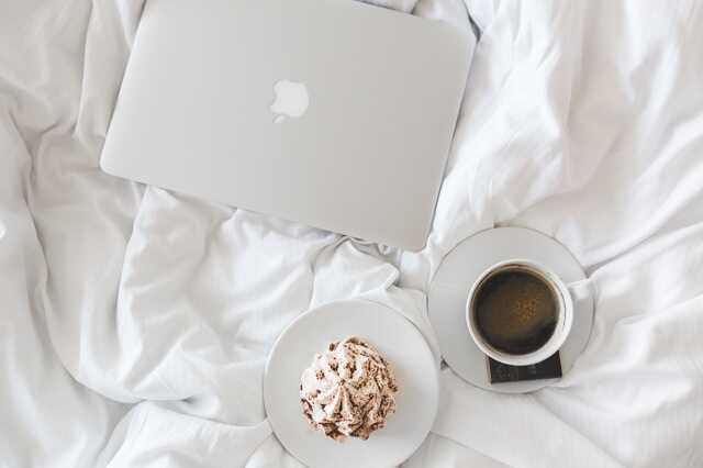 Flatlay of a laptop, coffee and muffin on a white duvet cover