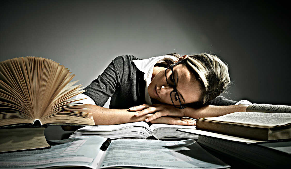 Young woman with glasses asleep on a table surrounded by books
