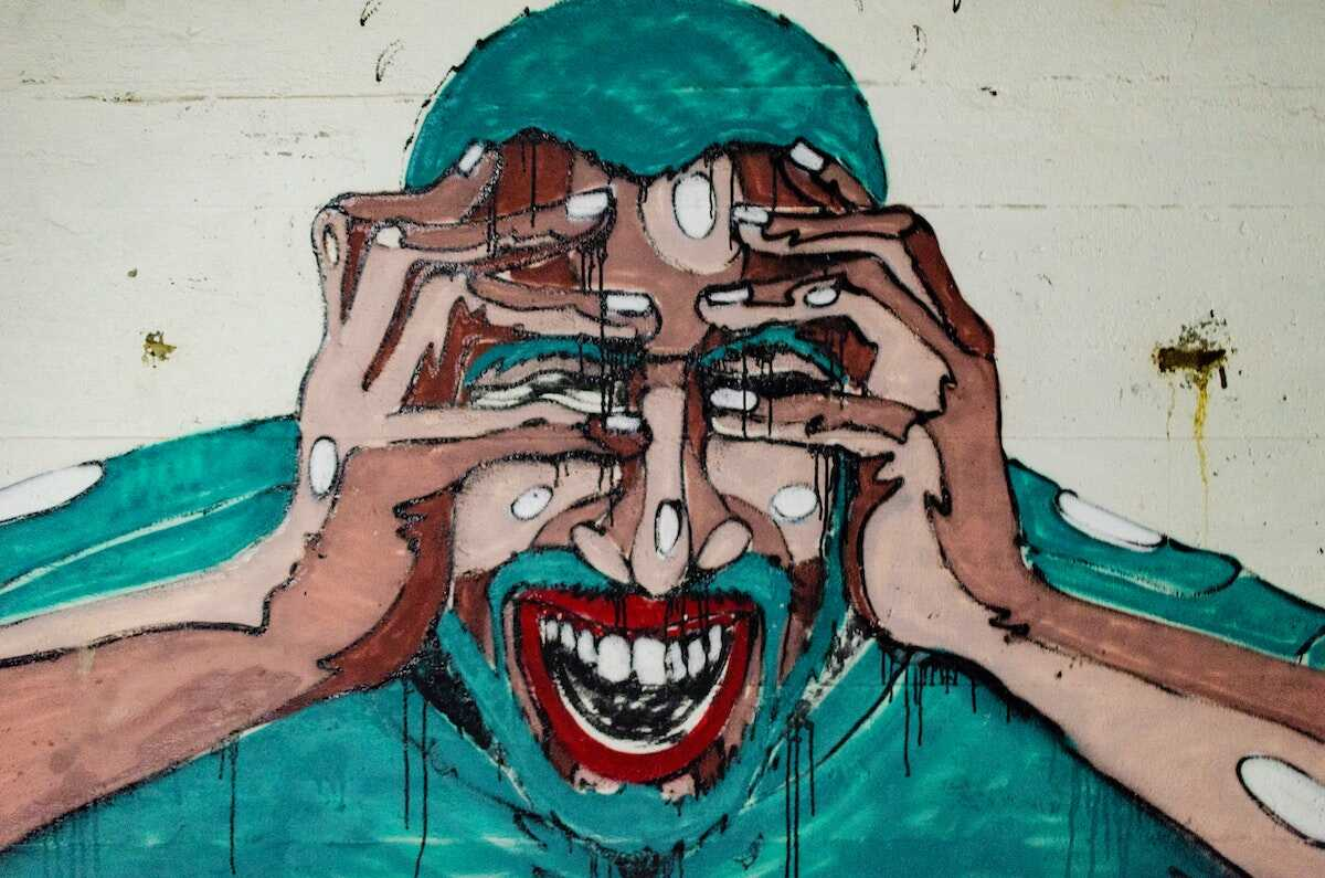 Grafitti picture of a screaming man with his hands over his eyes