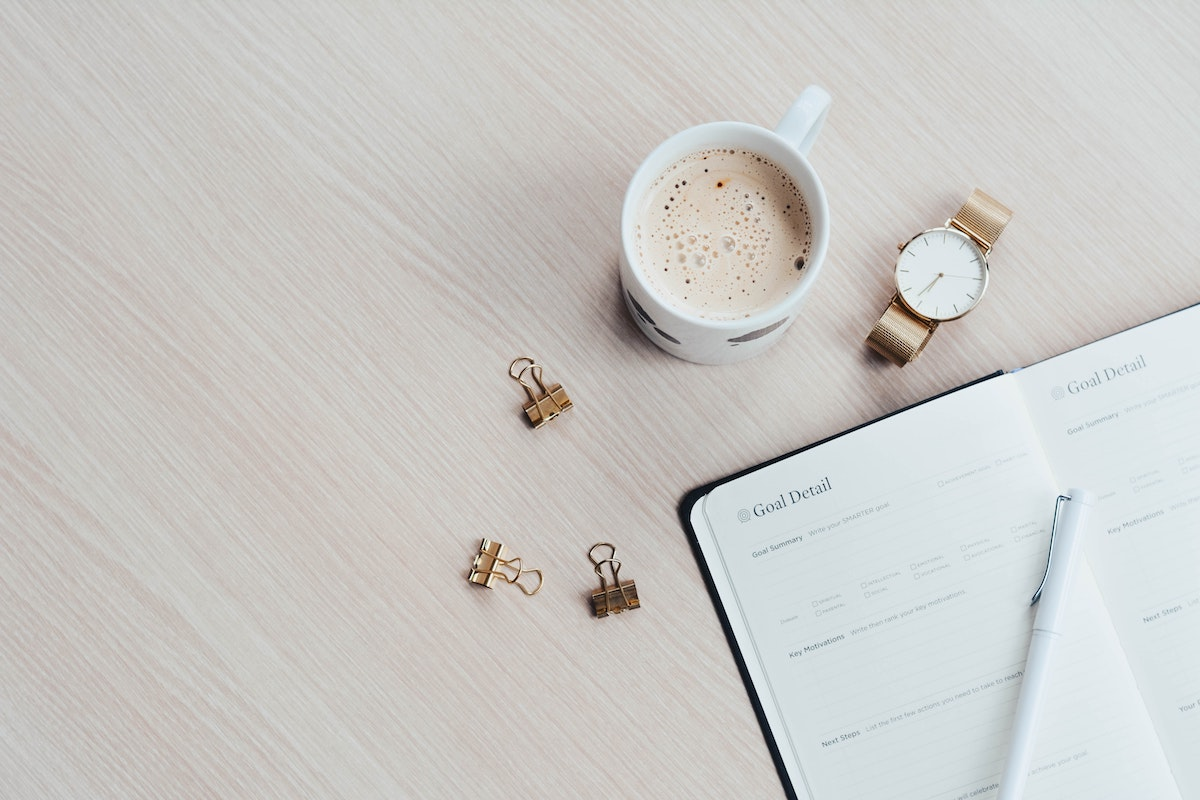 Flatlay of a table featuring an open goal setting notebook, gold watch and coffee in a mug