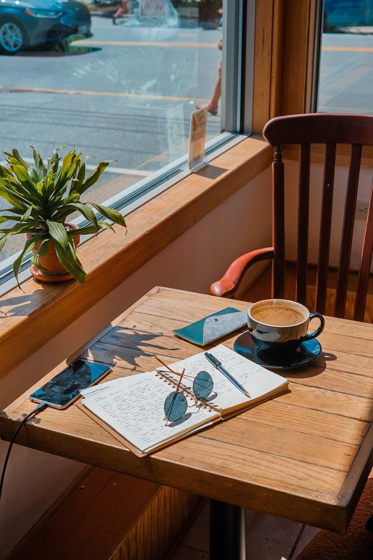 Sunny cafe table featuring an open notebook, pen, sunglasses, phone and empty coffee cup