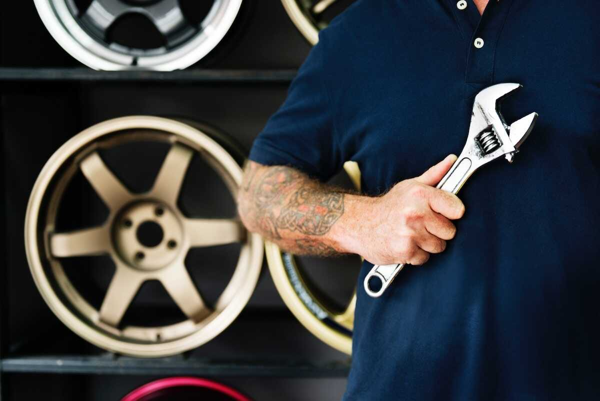 Tattoed hand holding a spanner