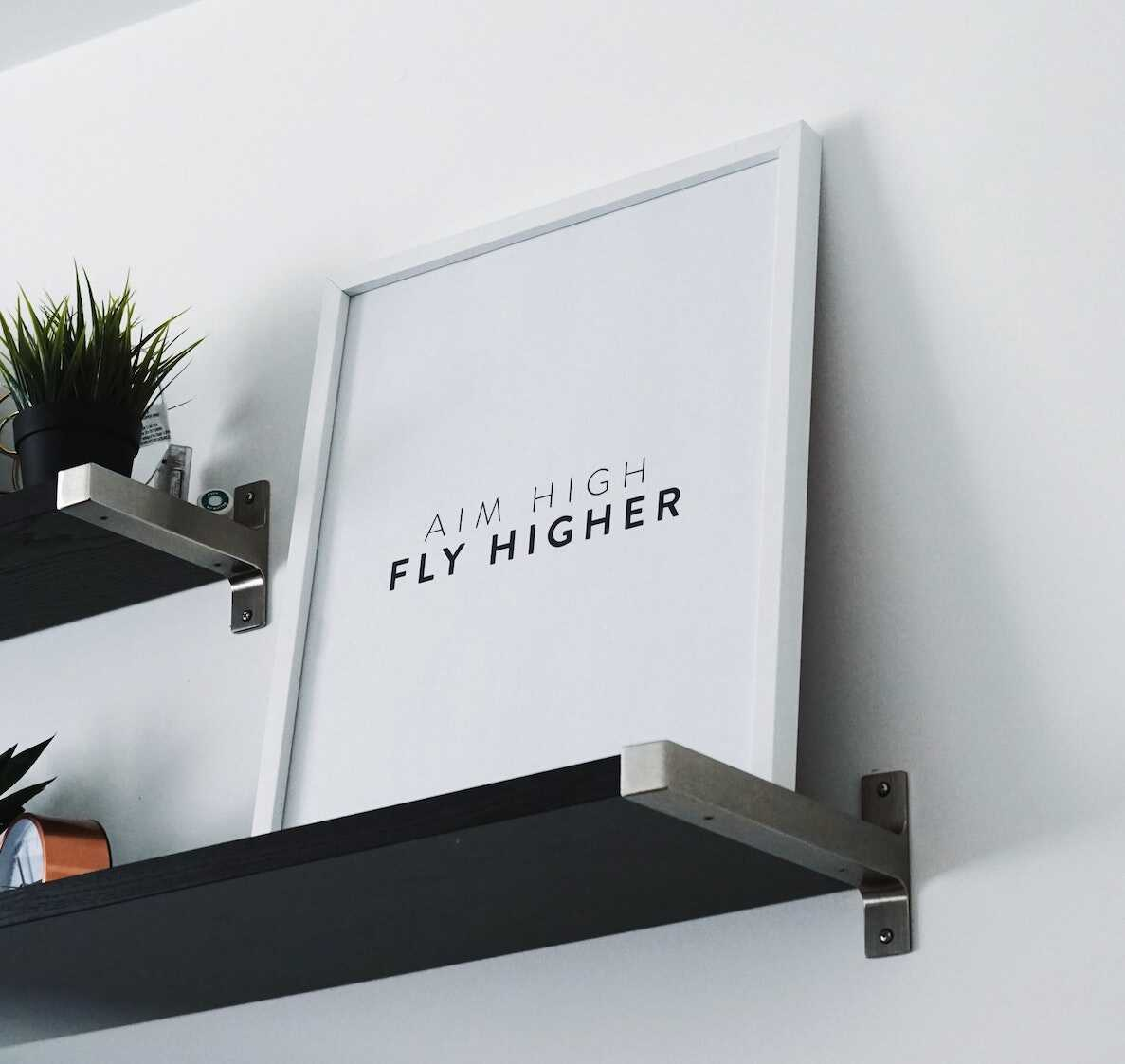 Picture with words Aim High Fly Higher on bookshelf