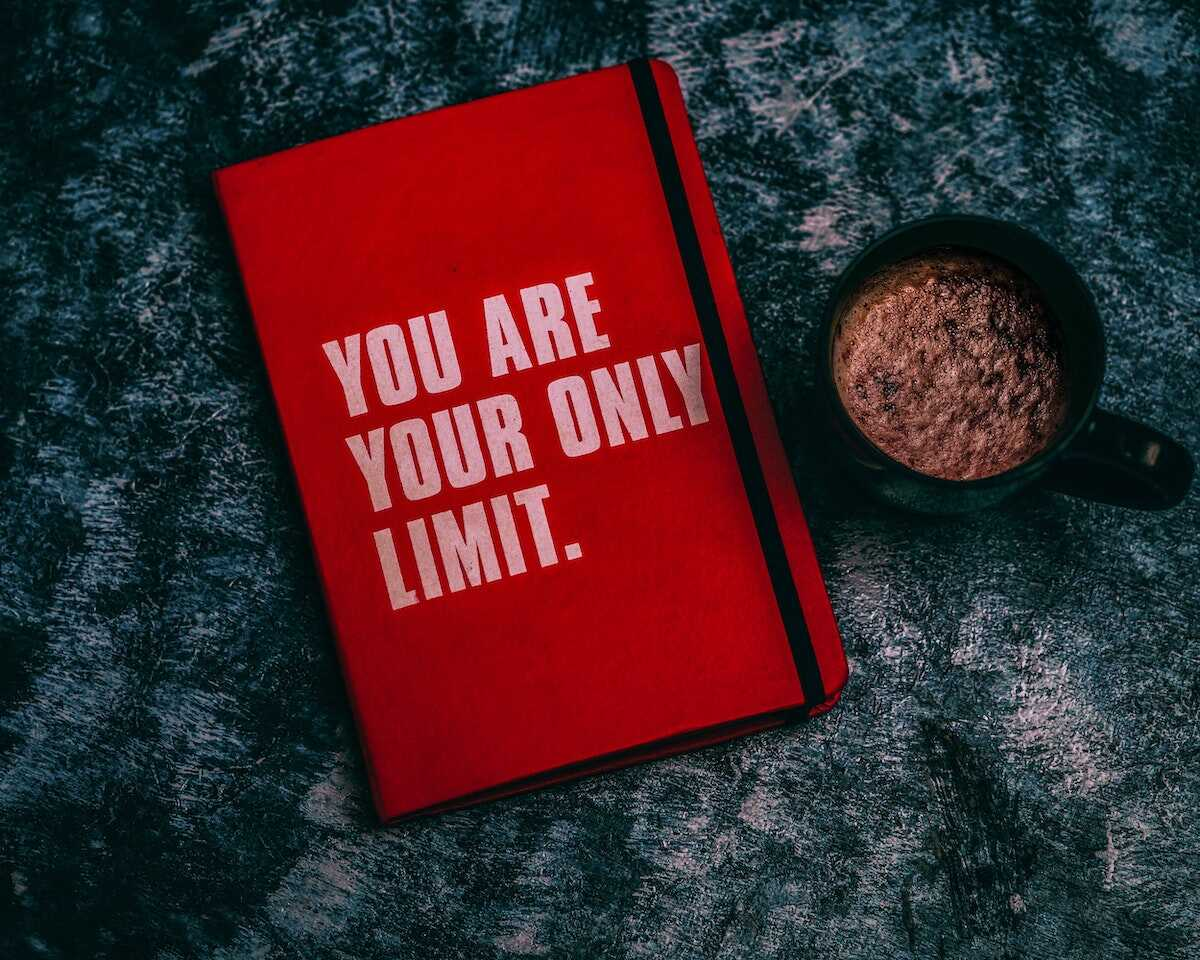 Red notebook with the words You Are Your Only Limit on a coffee table
