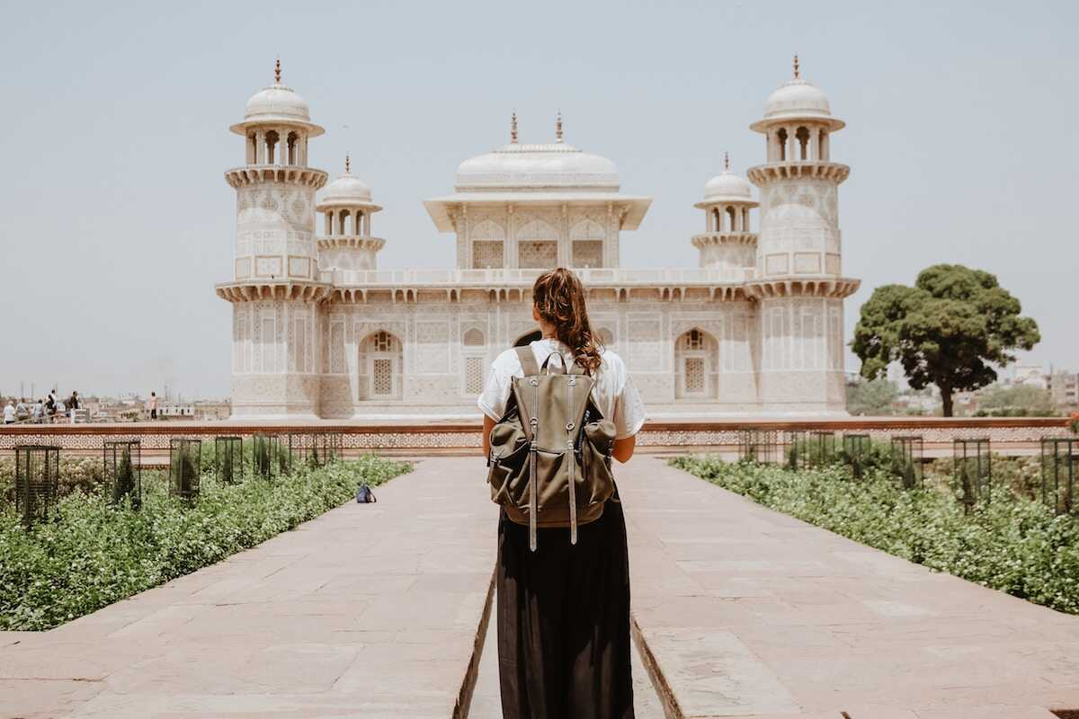 Woman with a backpack on holiday in India looking at a mausoleum