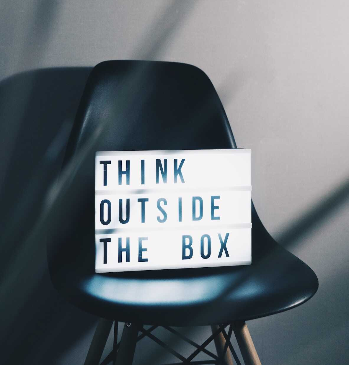 A bright sign saying Think Outside The Box sitting on a black chair