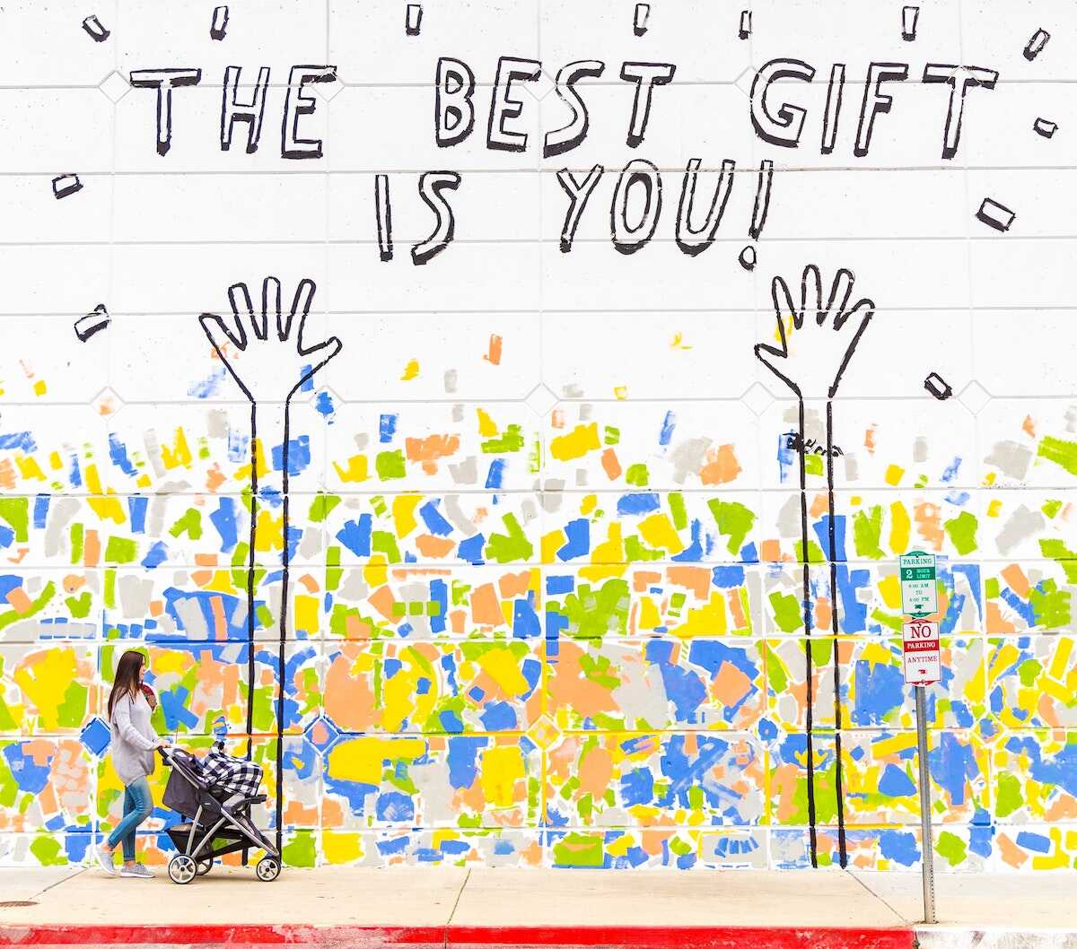 Woman with a pram walking past grafitti with the words The Best Gift is You