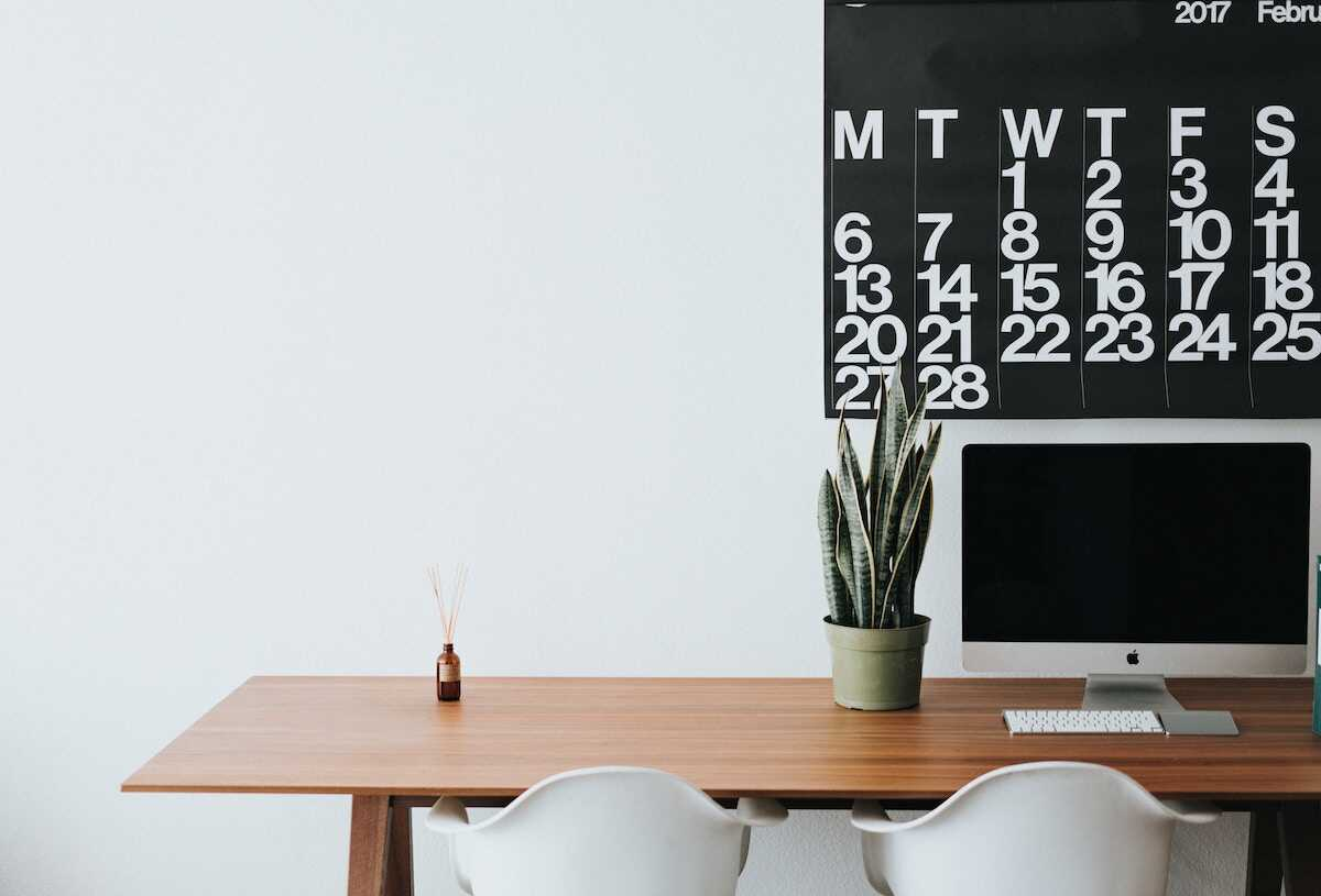Desk with an iMac, calender, plant and two white chairs