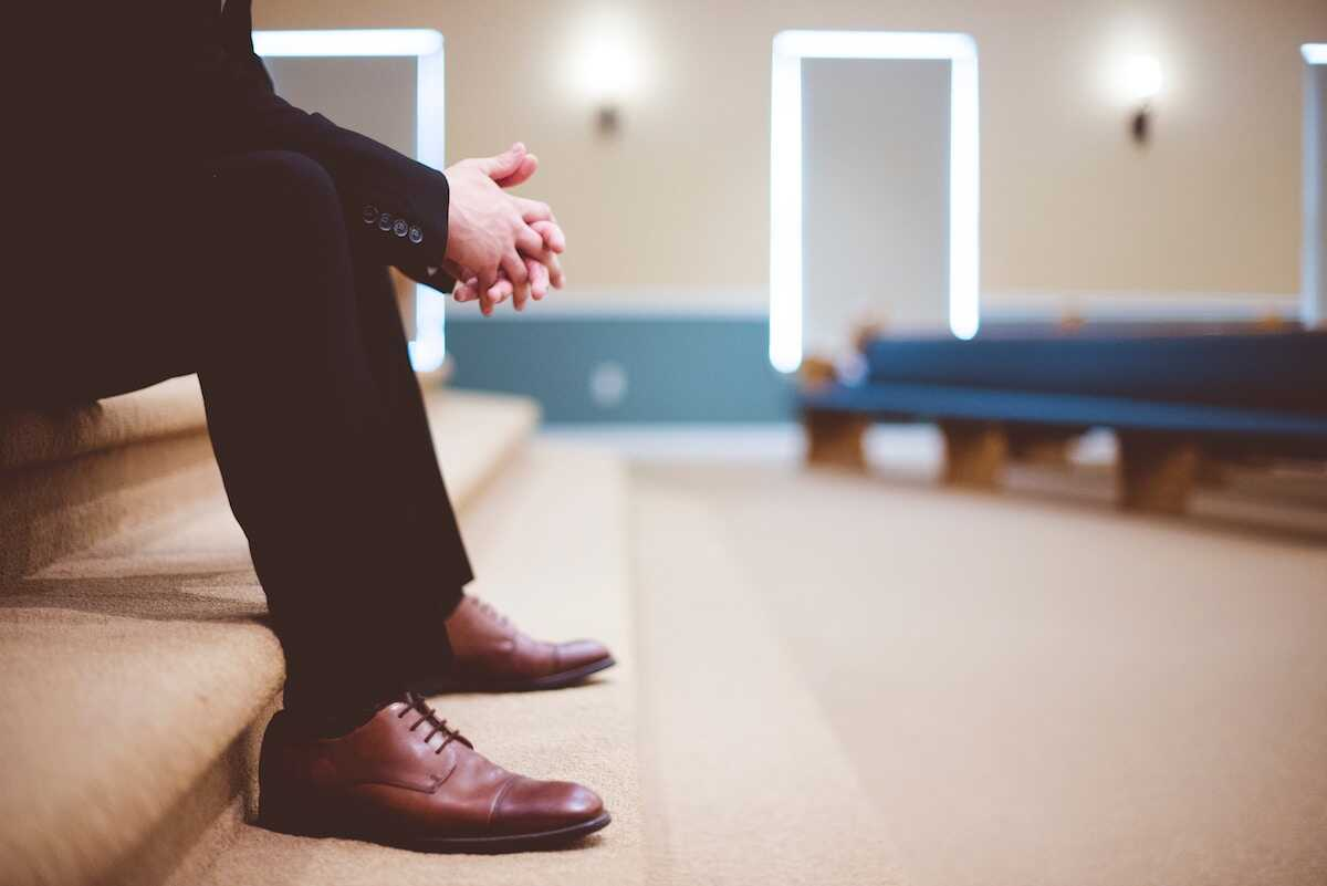 Man sitting on carpeted steps in front of church pews