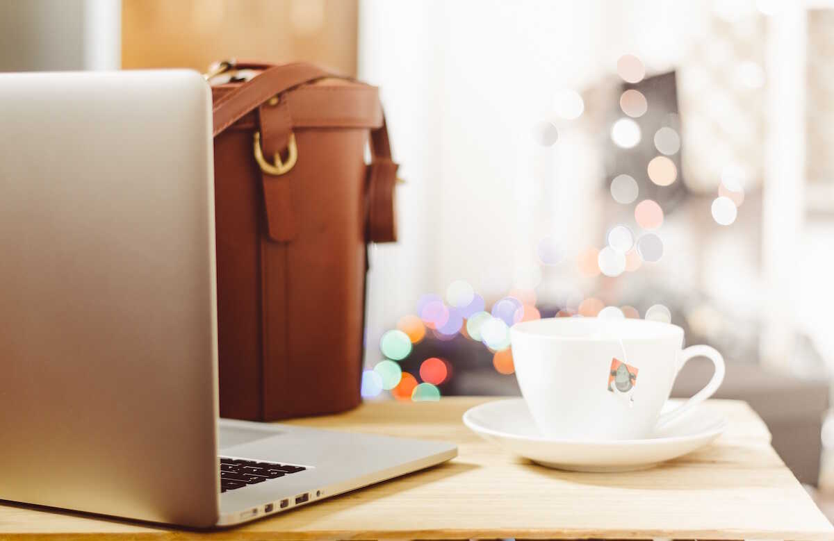 MacBook on a table alongside a white mug and leather bag