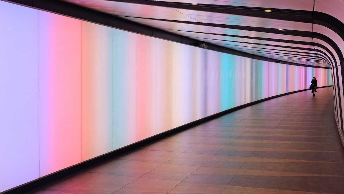 Woman walking through a coloured brightly lit tunnel
