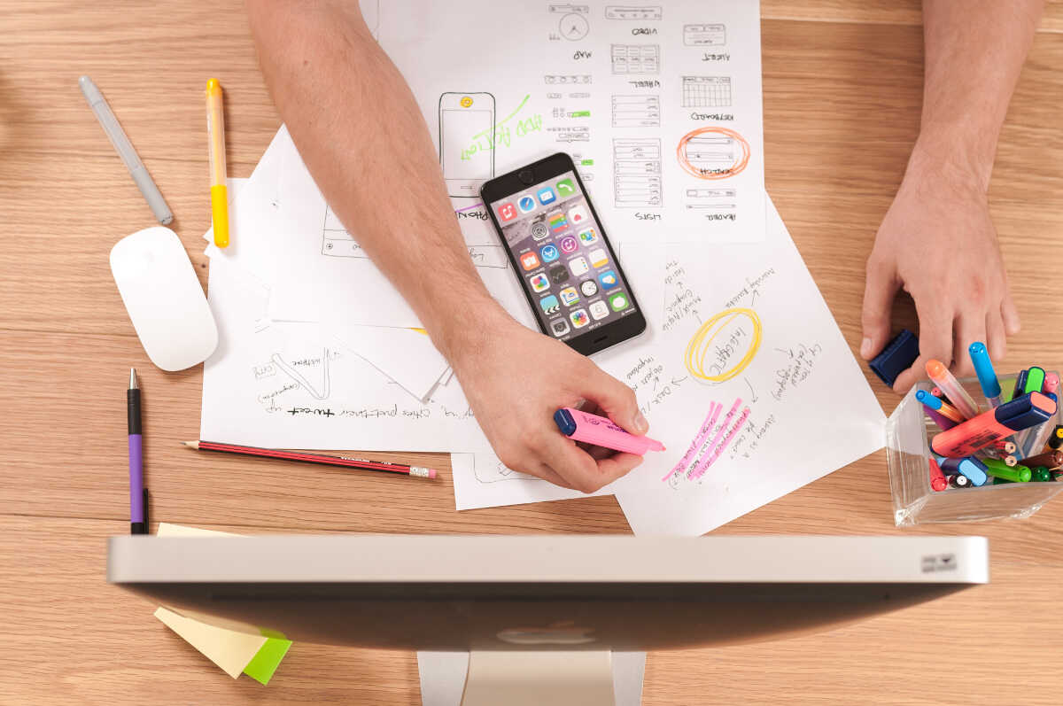 Person highlighting app plan drawings on a desk alongside an iPhone, mouse and pens