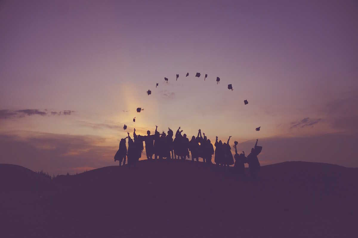 Purple image of graduates throwing their mortarboards up in the air making a semicircle