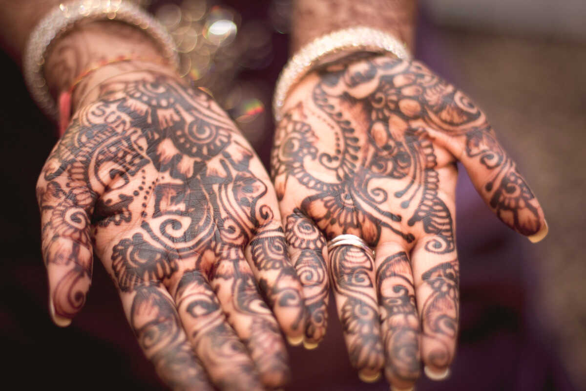 Woman's outturned hands covered in mehndi