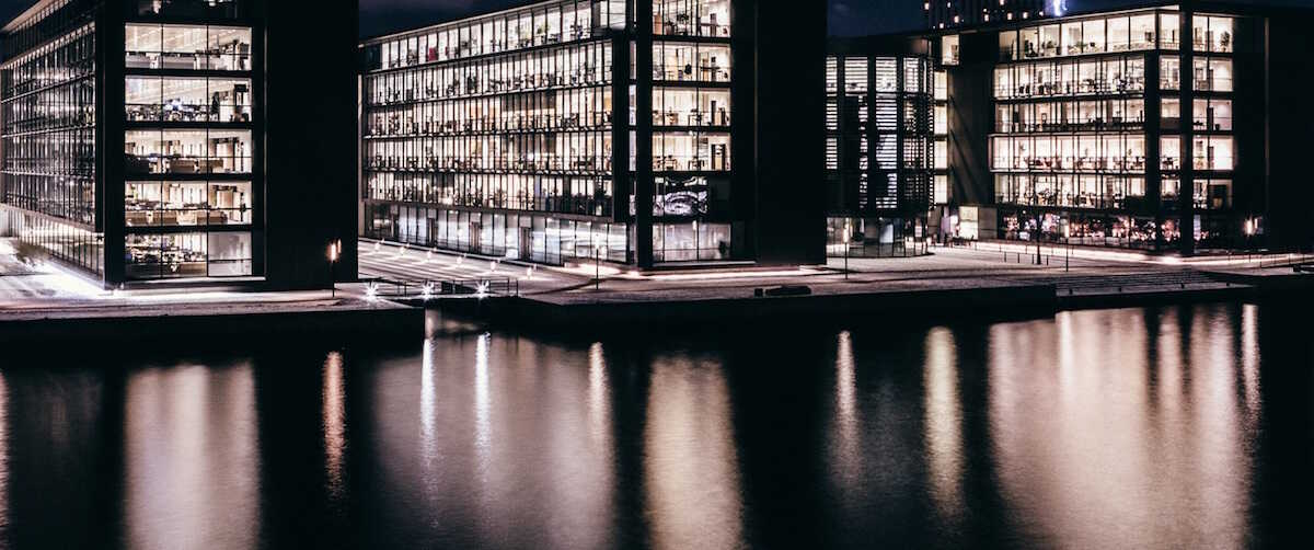Three plate glass office buildings taken across the water at night