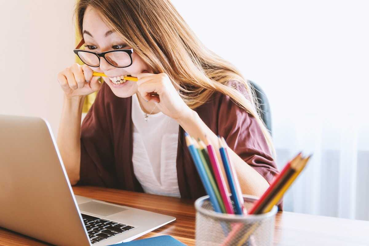 Stressed woman with a yellow pencil in her mouth looking at her laptop
