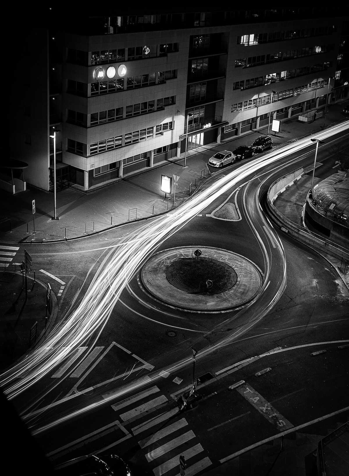 Black and white image of a roundabout with fast motion car lights